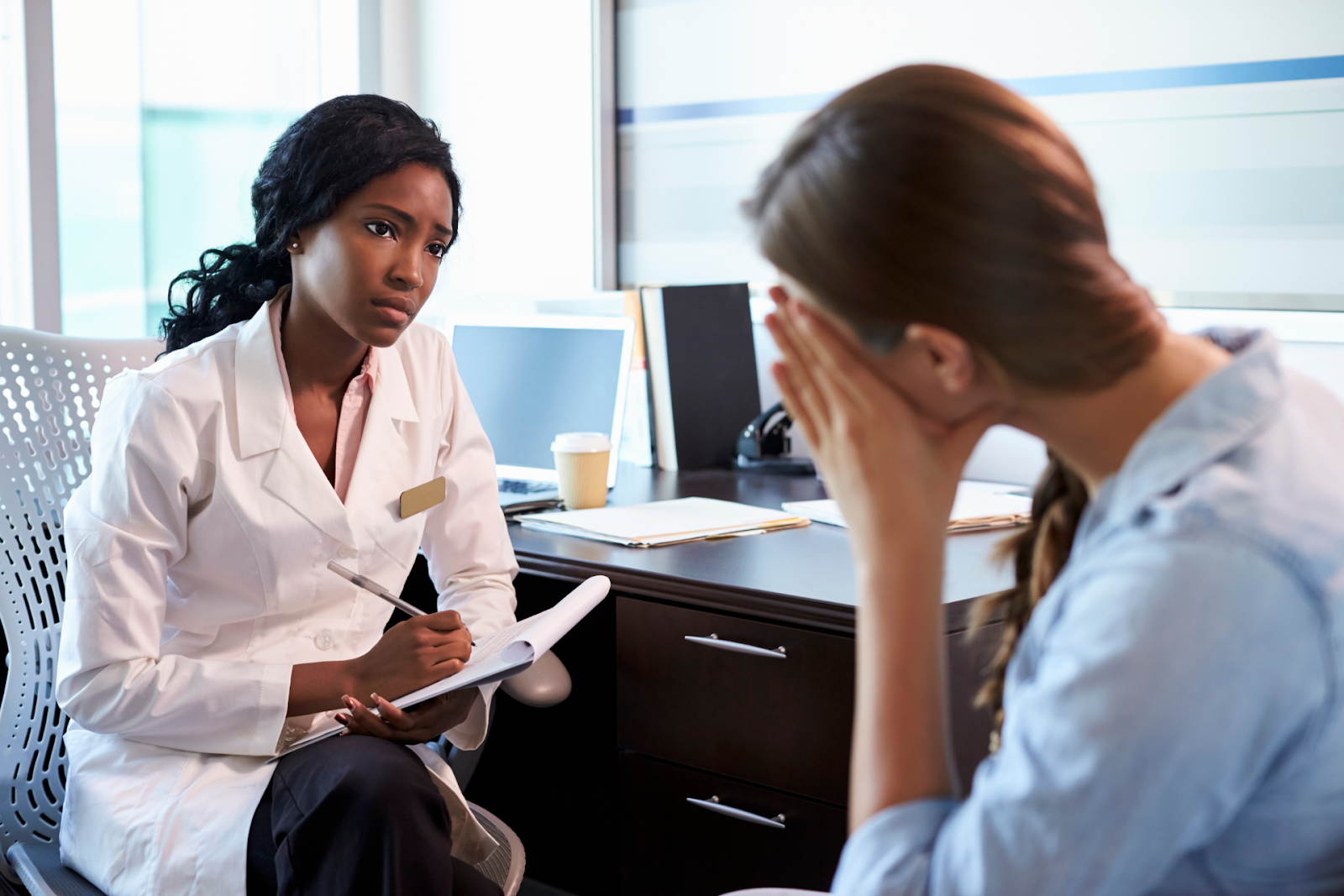 black female doctor talking to white female patient