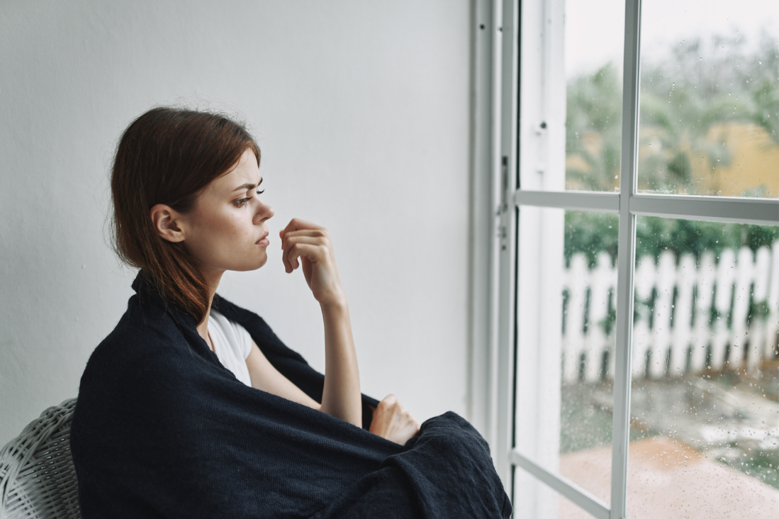depressed woman sitting by a window