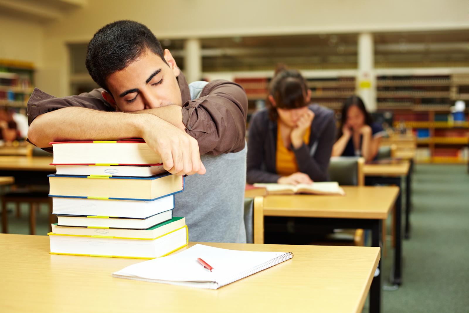 college student falling asleep on textbooks