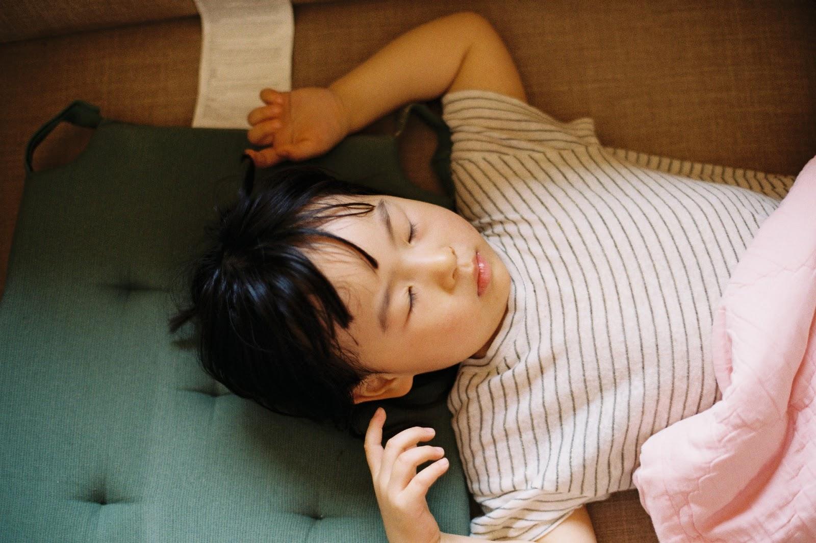 child sleeping on green sofa