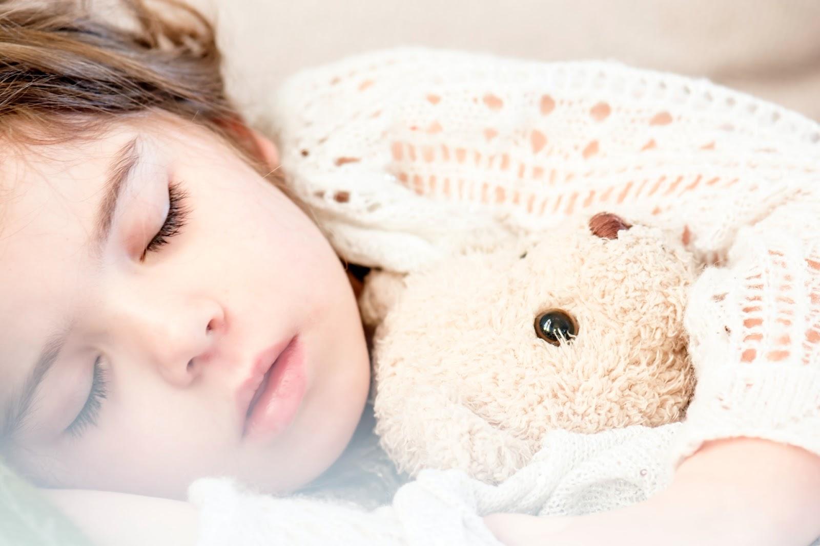 small girl sleeping with bear