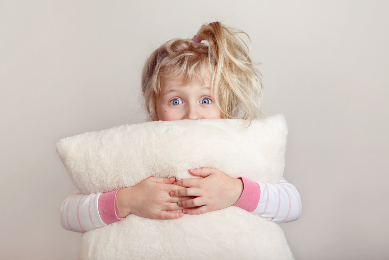 small girl holding pillow