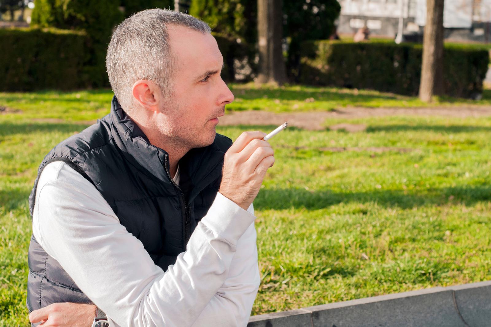 business man smoking sitting on a street sidewalk