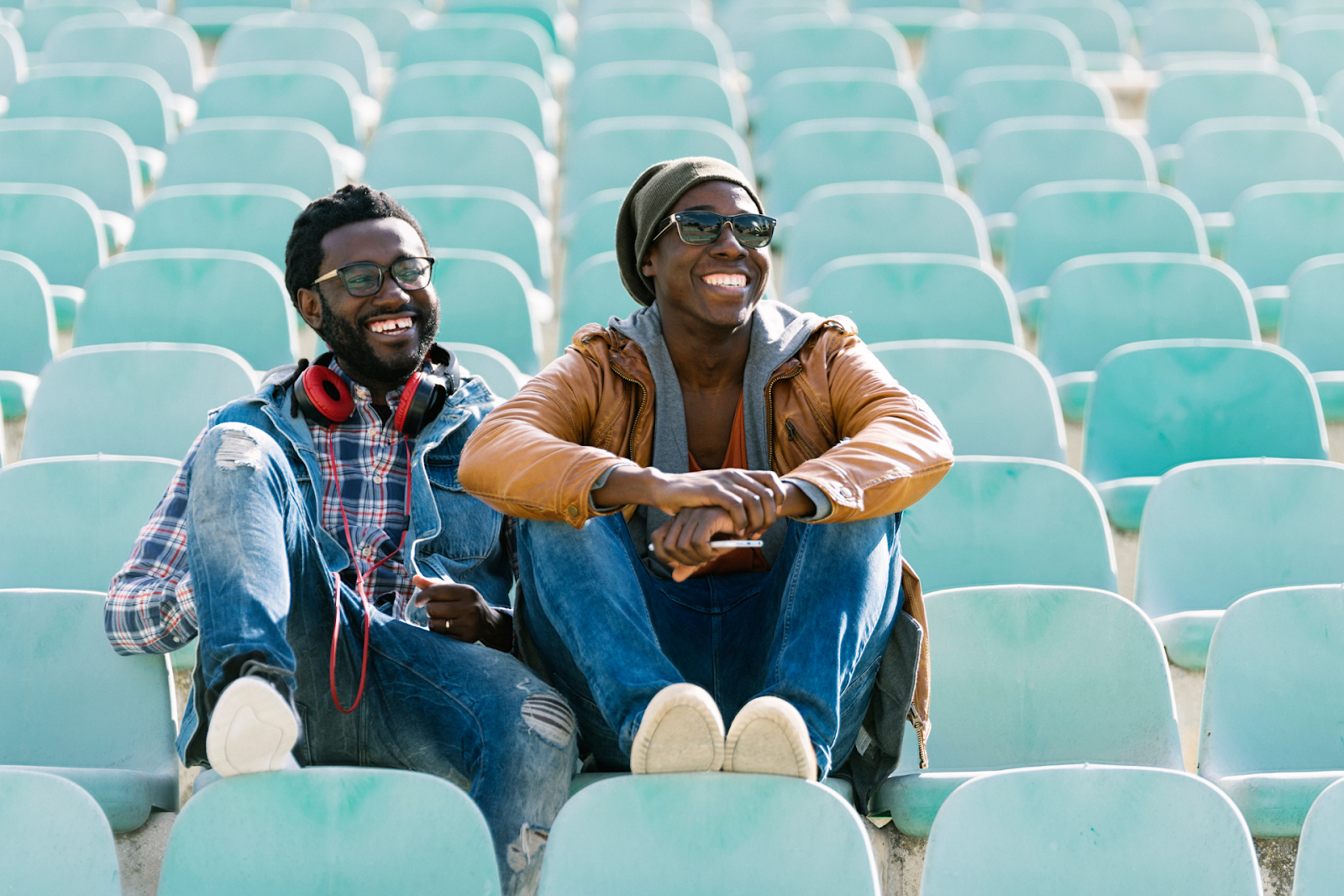 two black friends sitting next to each other in bleachers