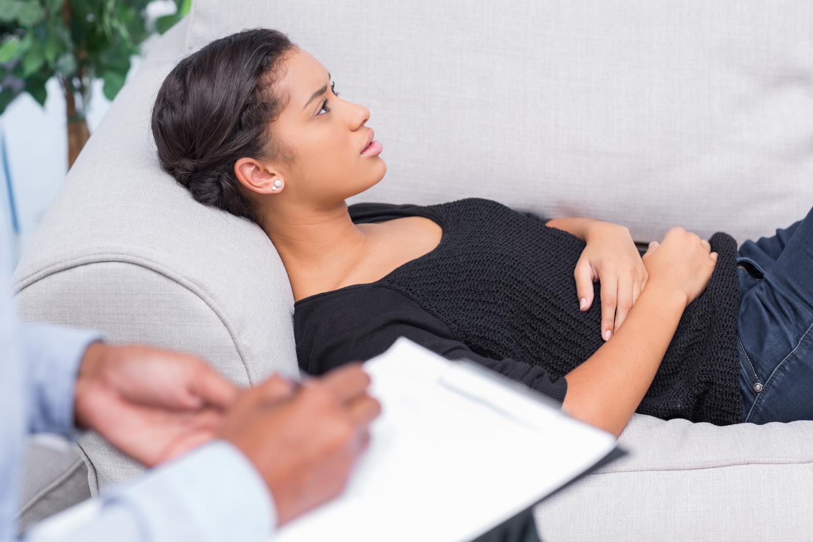 woman lying on sofa talking to therapist