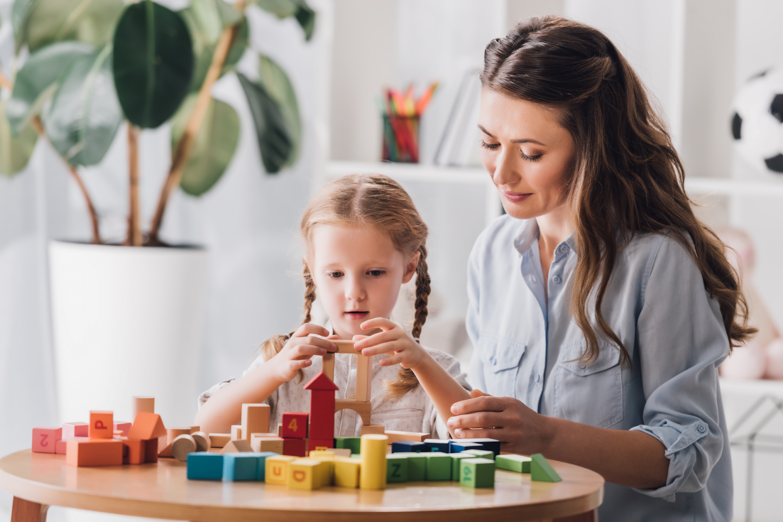 child playing with blocks next to mother