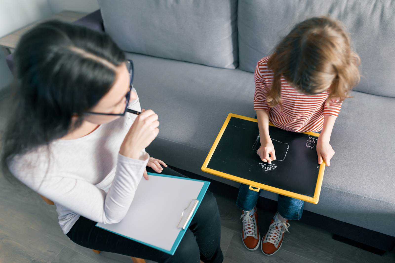 girl drawing on chalkboard next to psychologist