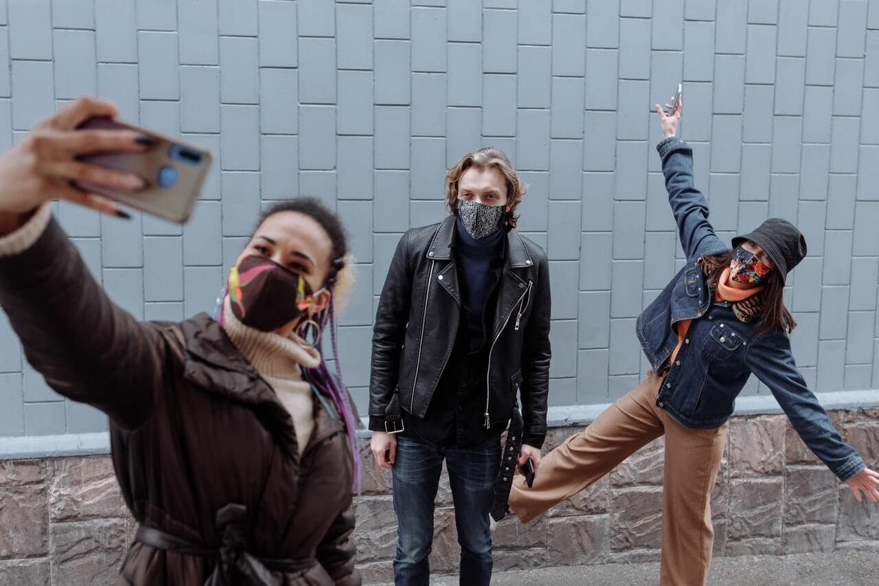 three young people taking a selfie wearing masks trendy clothes on the sidewalk jackets