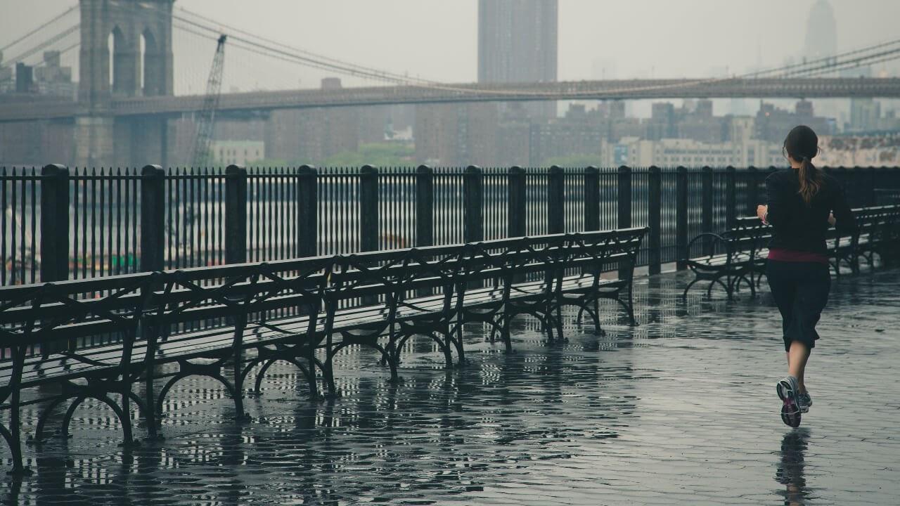 woman jogging gray skies new york city brooklyn bridge rain
