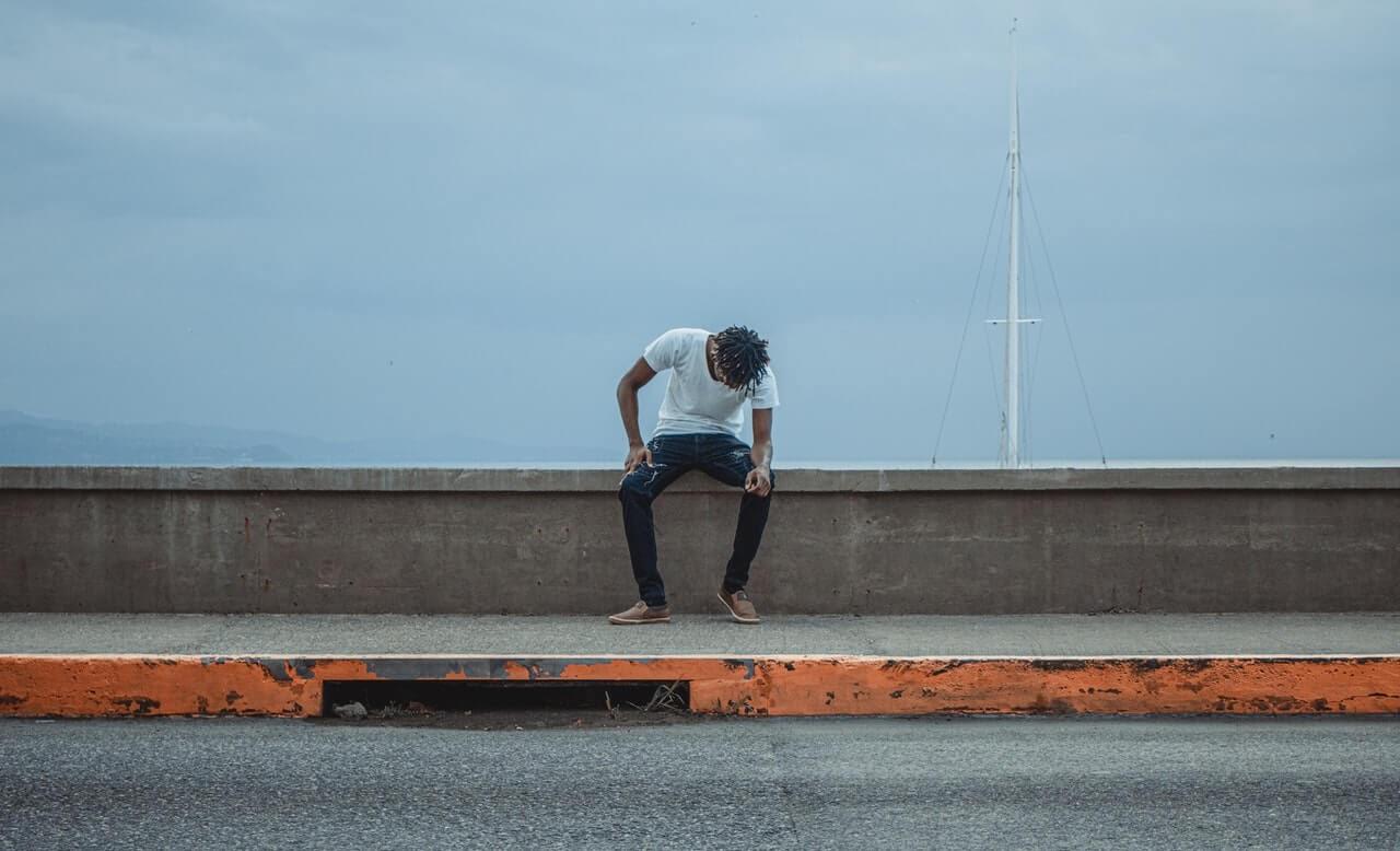man sitting on bridge looking sad sailboat blue sky