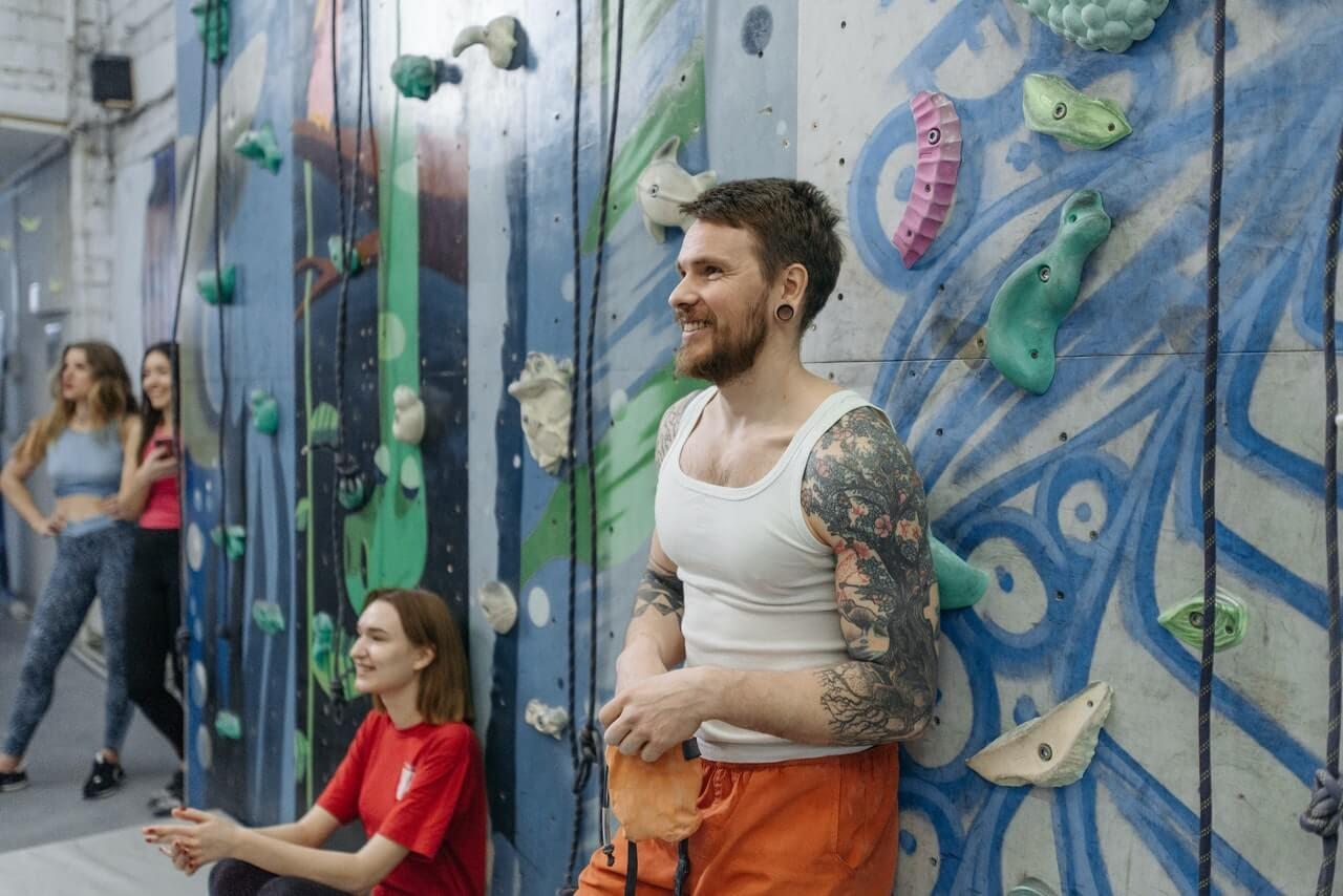 rock climbing wall happiness activity smiling man tattoos women gym class