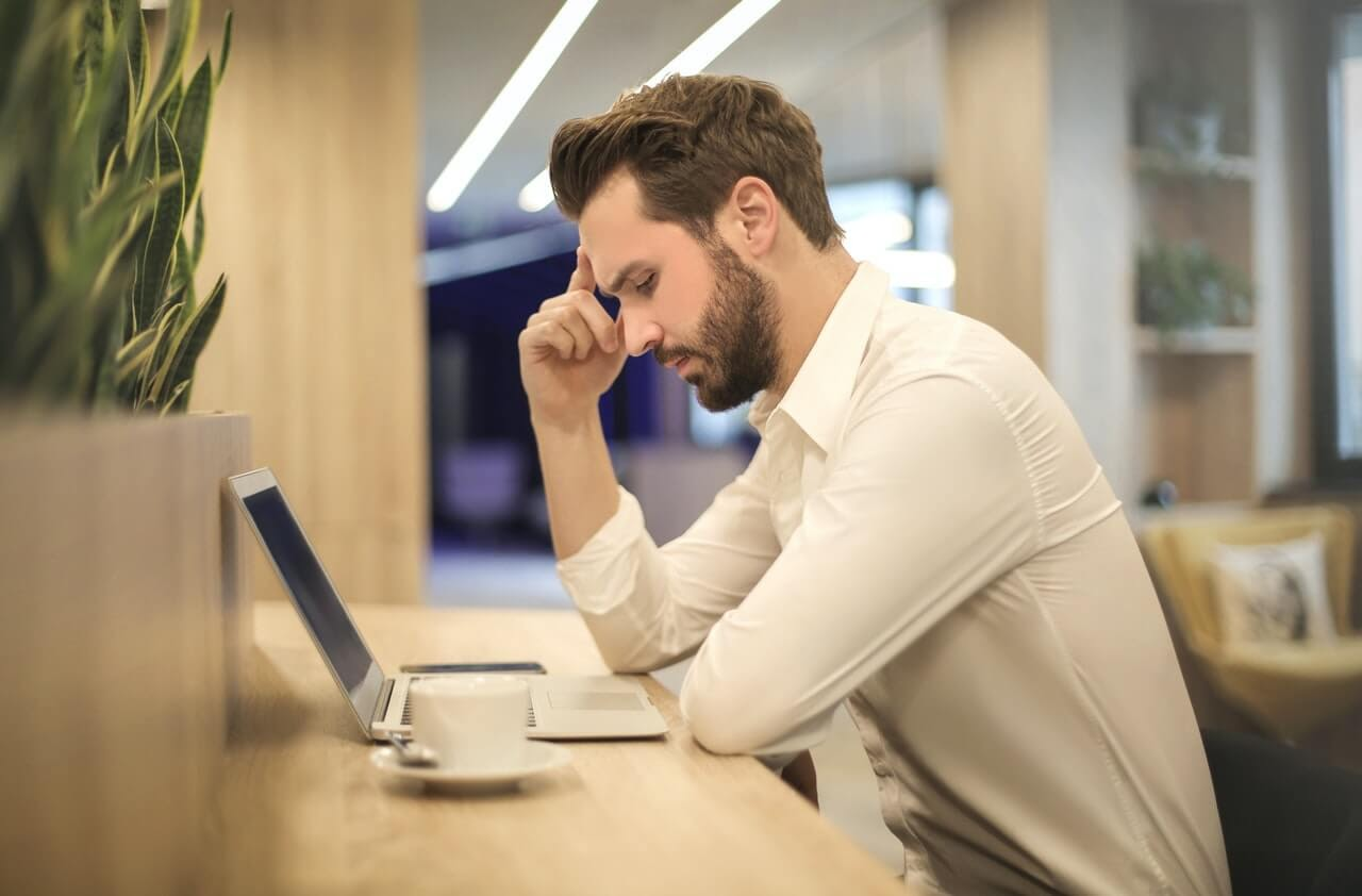 man distressed working research laptop white shirt office