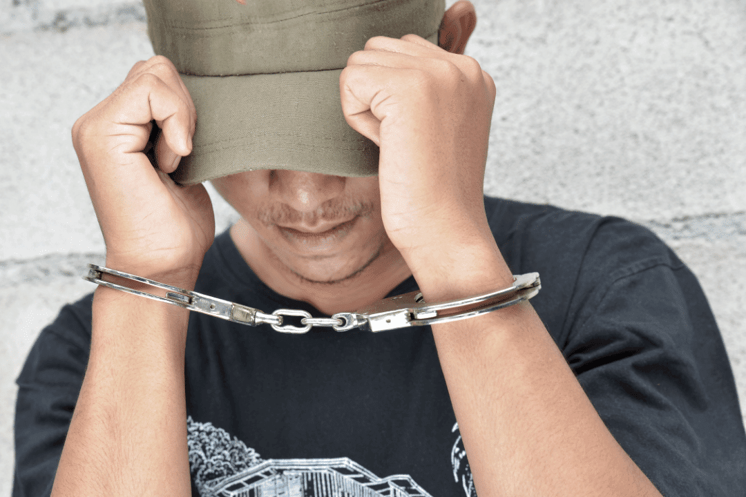 man in handcuffs green hat black shirt outside addiction chains