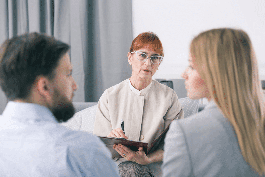 therapist with red hair counseling couple concerned look gray curtain white room clipboard