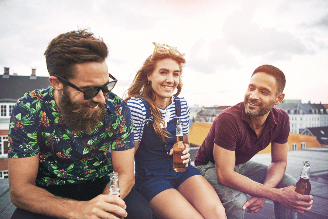 three friends drinks rooftop smiling sunglasses two men one woman trendy clothing clouds