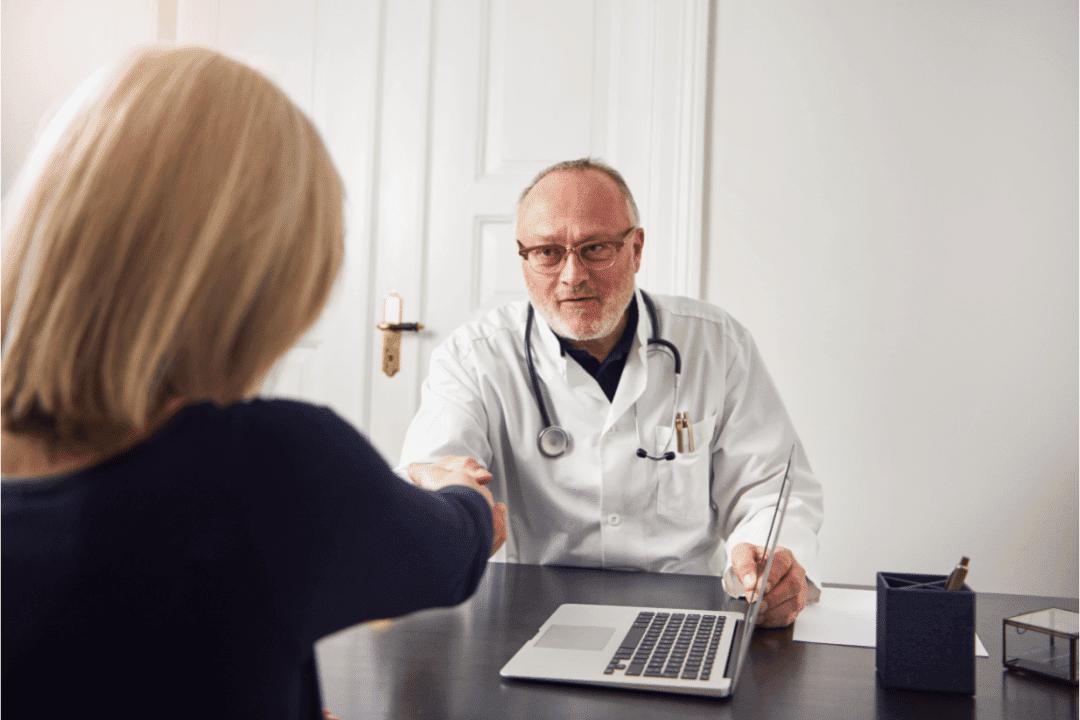 older doctor shaking hands with mother laptop office lab coat stethoscope desk