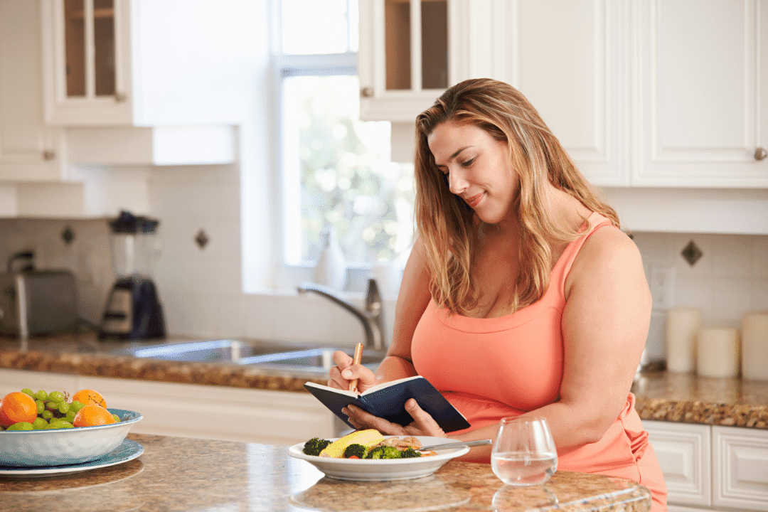 woman in kitchen exercise clothes breakfast water journaling orange black journal fruits and vegetables