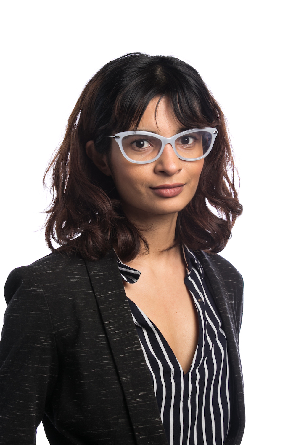 A headshot of an Indian woman with wavy brown hair (a balayage). She is wearing a black blazer speckled with lines and a V-neck navy blue pinstripe blouse. She also has on big, light blue cat-eye glasses.