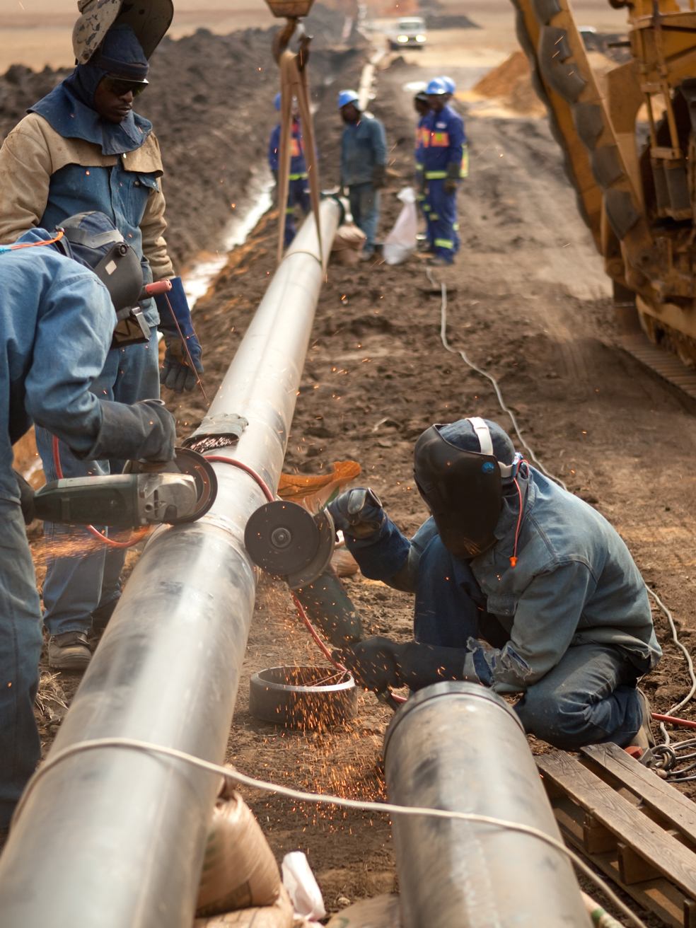 A crew of workers assembling an oil pipeline