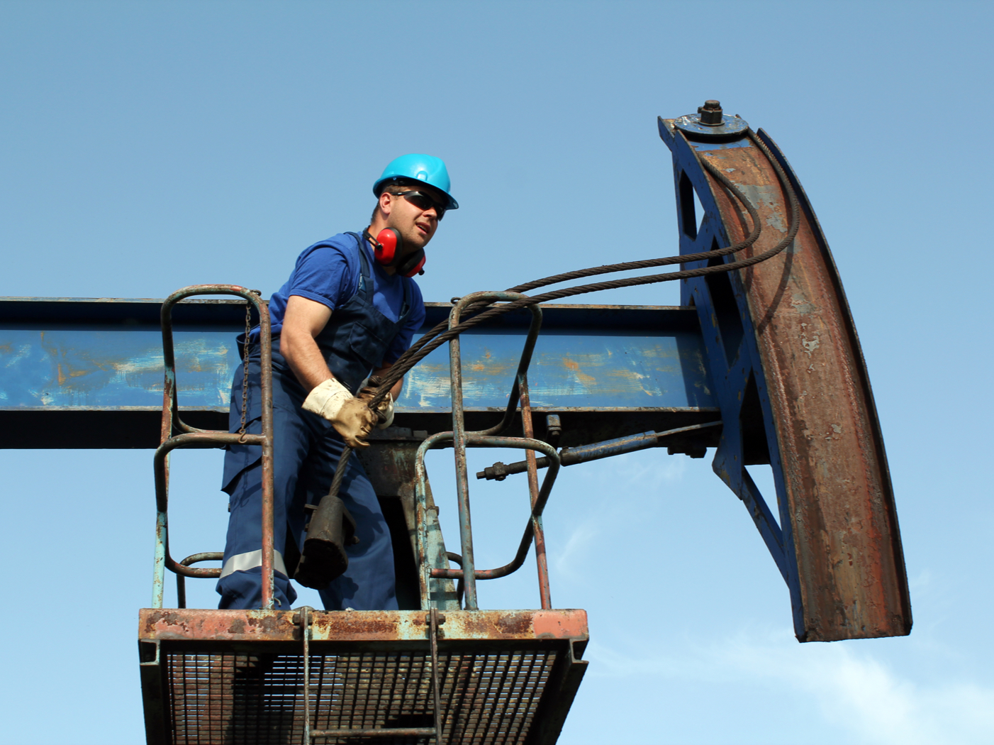 A worker making repairs on an oil pump jack