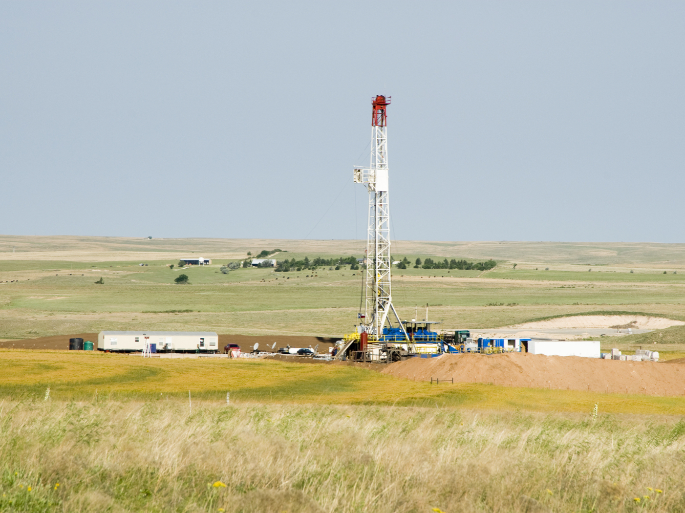 An oil well towering above a mostly empty plain of grass