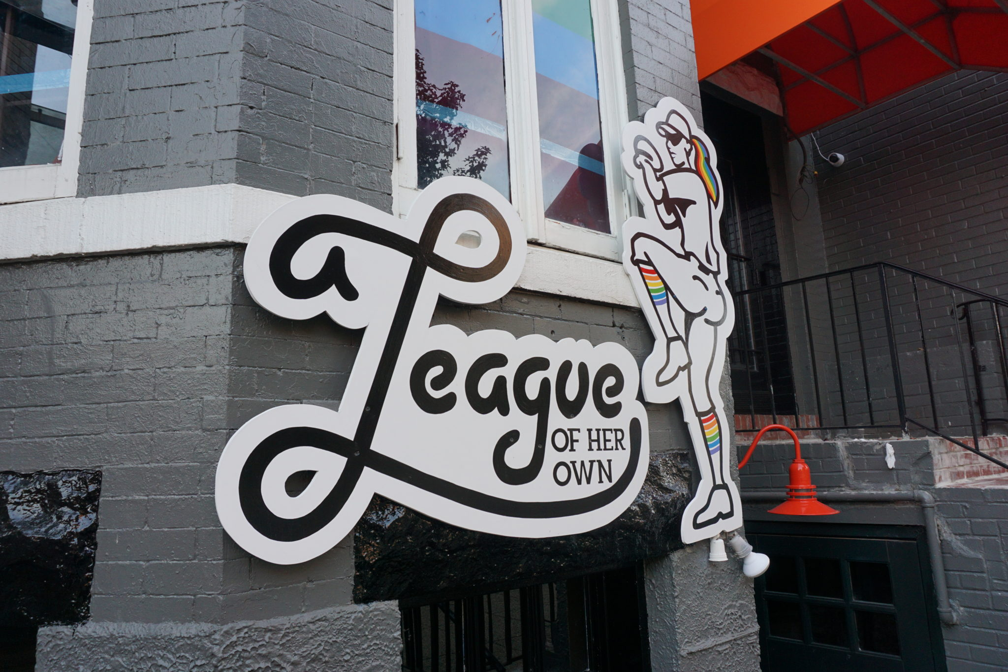 Black and white versions of the Pitchers and League of Her Own logos on the gray brick exterior of the bar