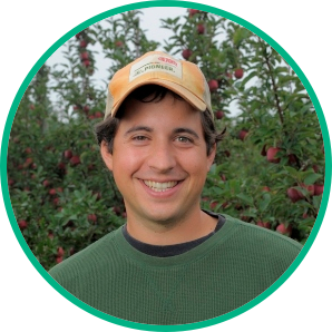 Brett Schuyler from Woolleys' Lamb headshot in an apple orchard