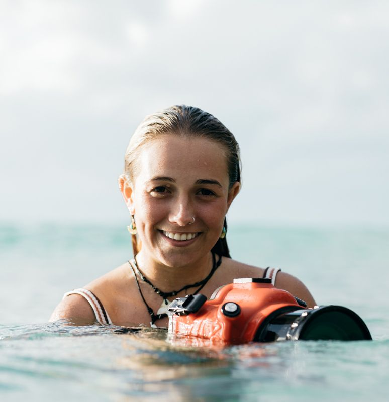 A girl in the water holding camera in underwater housing