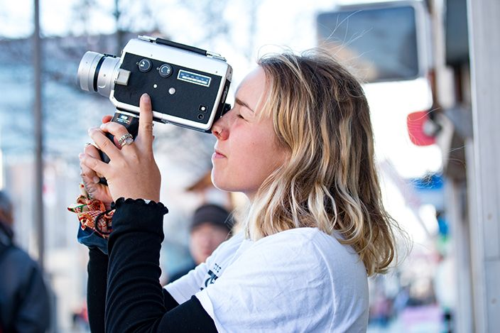 girl looking through view finder of a Super 8 Film Camera