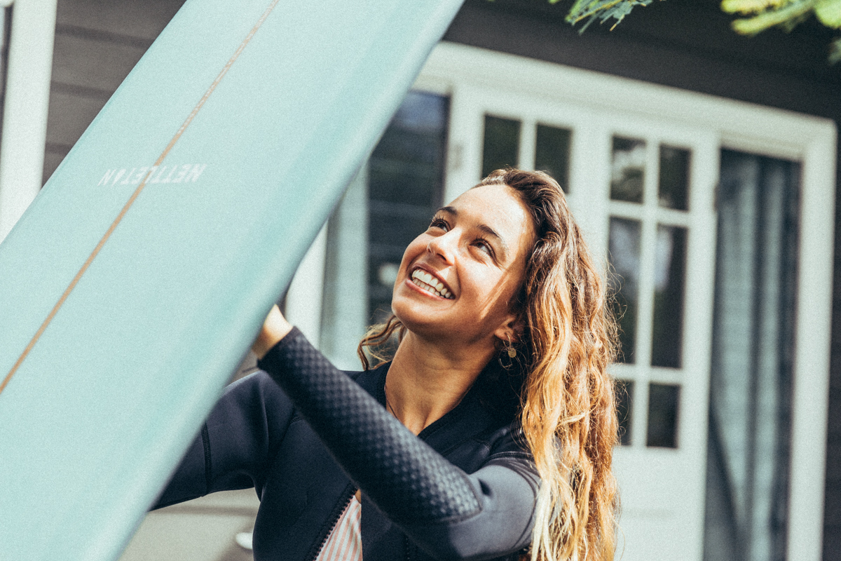 A girl smiling looking at a surfboard