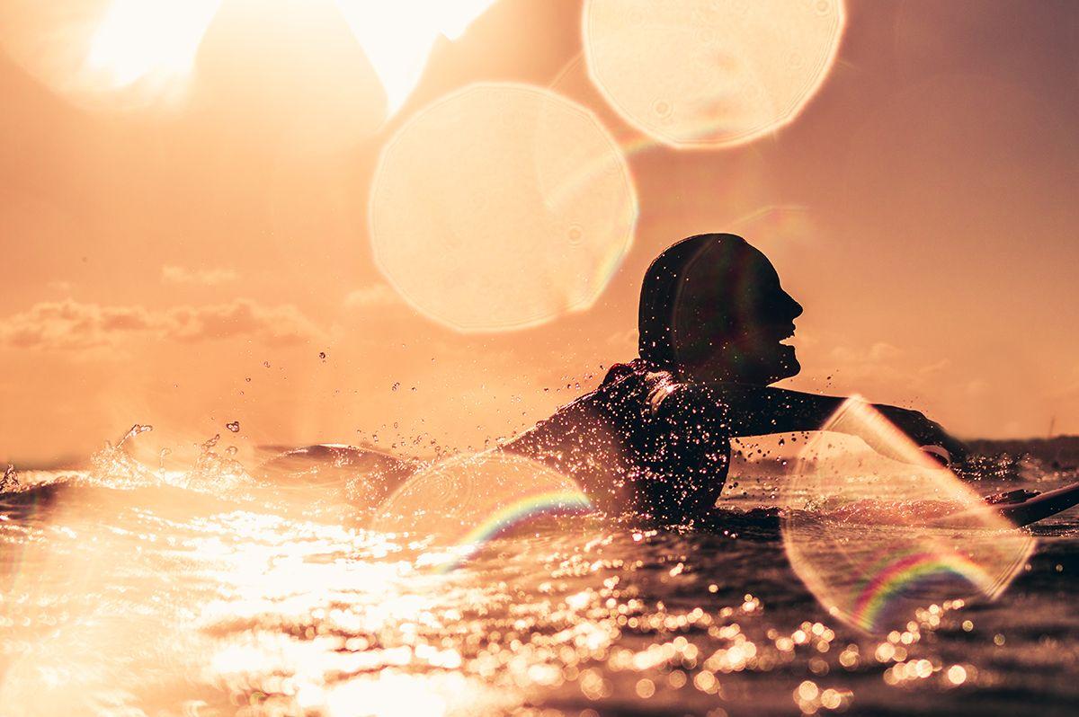 A girl paddling at sunset