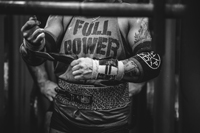 Female powerlifter putting on her wrist wraps