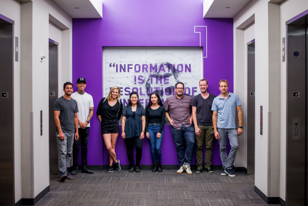 Group photo of Anthony, Gio, Brie, Carol, Chanelly, Bradfor, Sean, and Steve in front of first floor elevator installation at the unveiling ceremony at Qualcomm