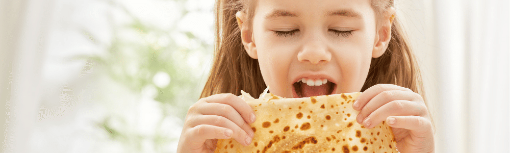 Closeup of girl biting into a tortilla