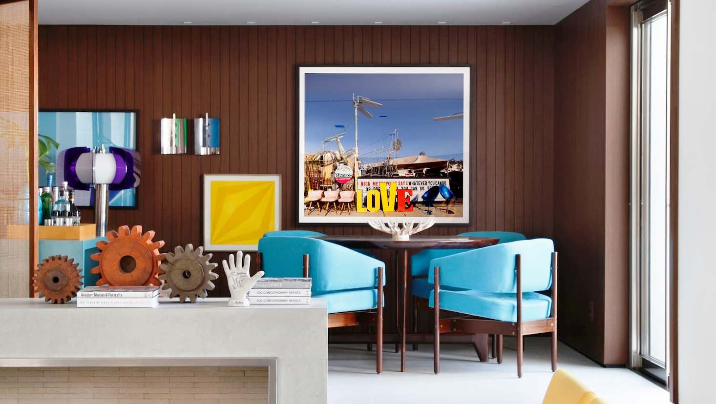 Dining area with a round brown table surrounded by upholstered turquoise chairs. On the wall are pictures of different heights in yellow, white, and azure.