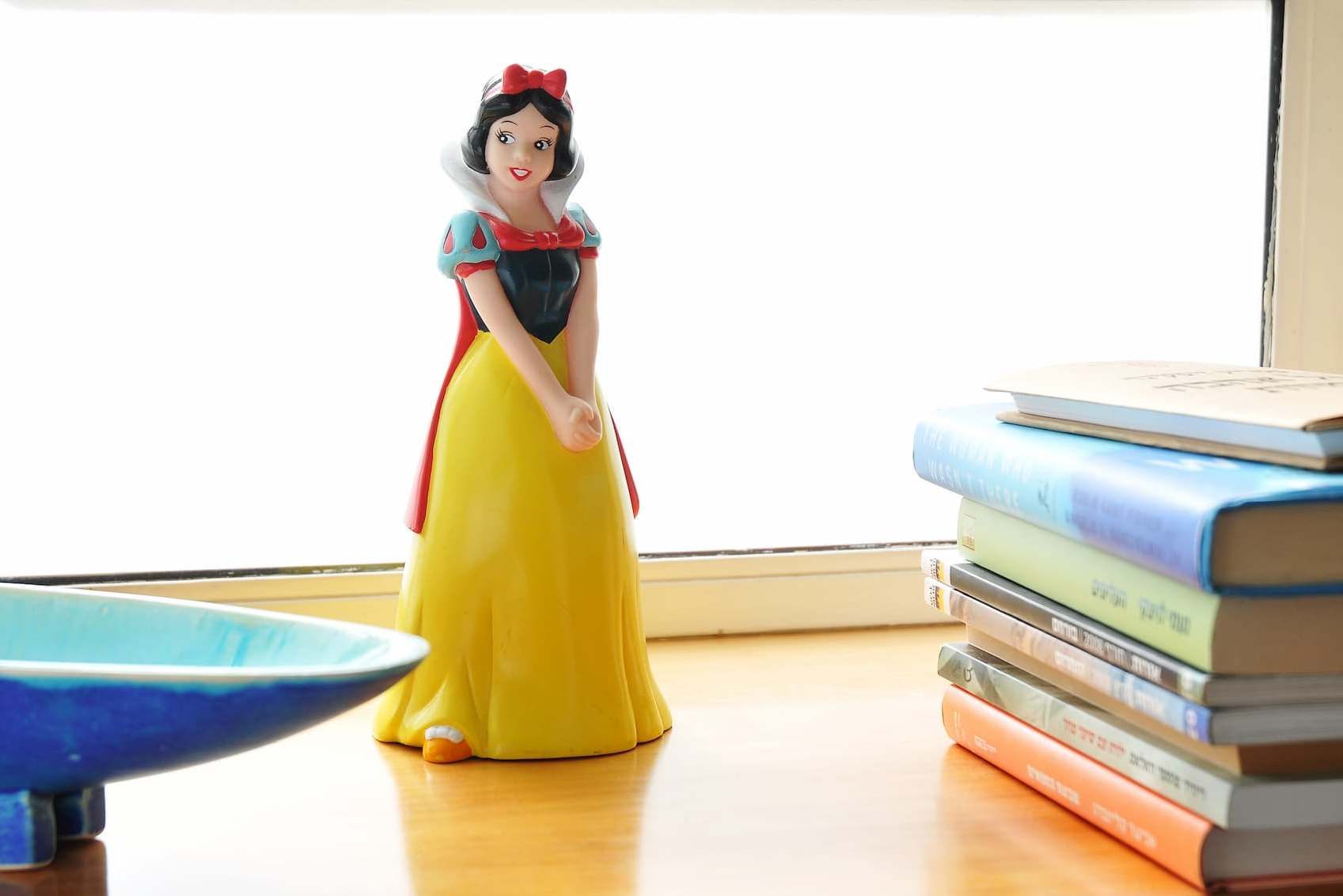 A smiling Cinderella figurine with a yellow dress and a red ribbon perched on a softly-lit wooden surface