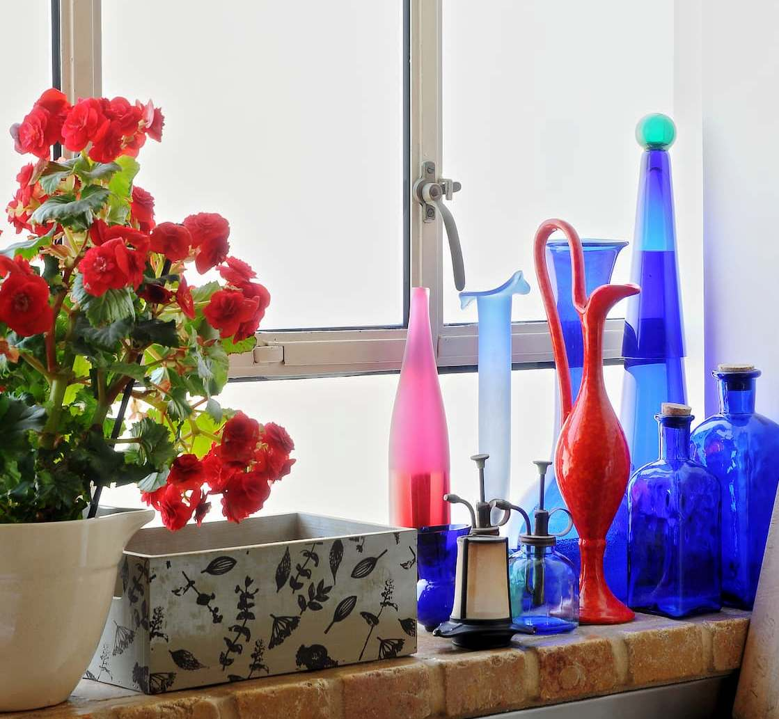 Glass bottles in shades of blue and red on a windowsill next to a red geranium flower pot