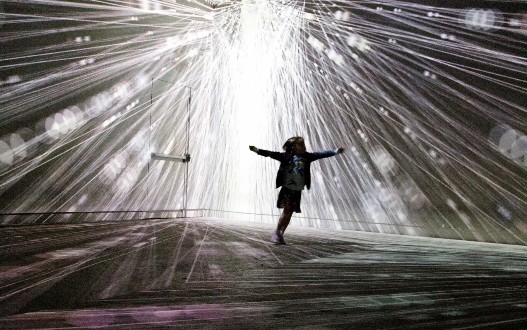A boy running with arms outstretched in space where lighted wires stretch out in all directions from above