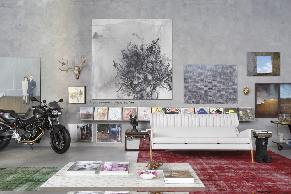 A young-looking living room with various records displayed along a shelf and square pictures of different sizes displayed above it.  A sofa, a table, and two carpets are aesthetically pleasing despite their seemingly random placement, and a motorcycle stands in the corner at a slight angle