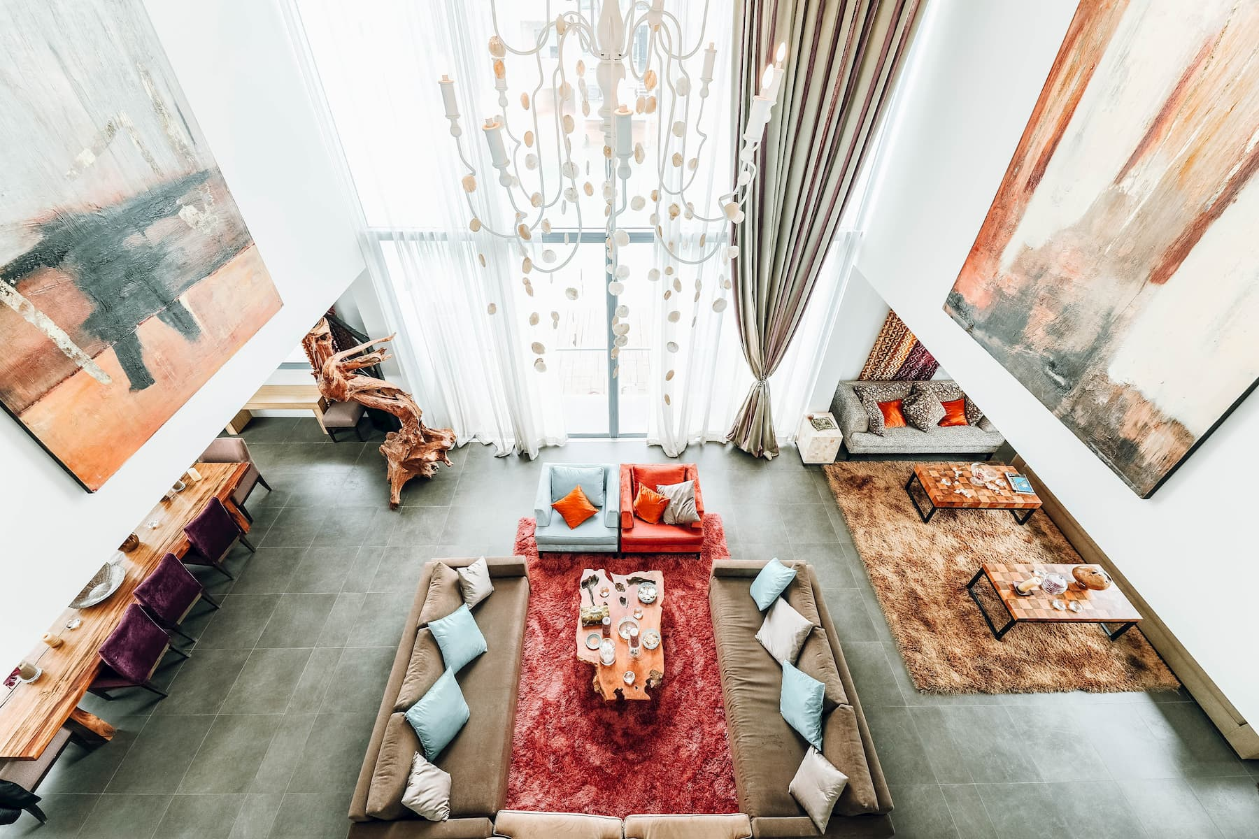 Overlooking a large living room with sofas, armchairs, and shag carpets in red and earth tones