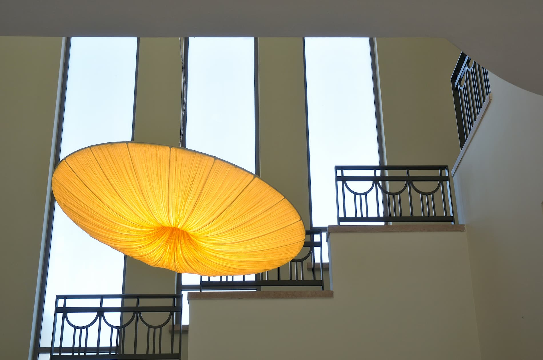 A large round light fixture made of folded fabric hangs in front of a staircase against a wall with three tall rectangular windows.