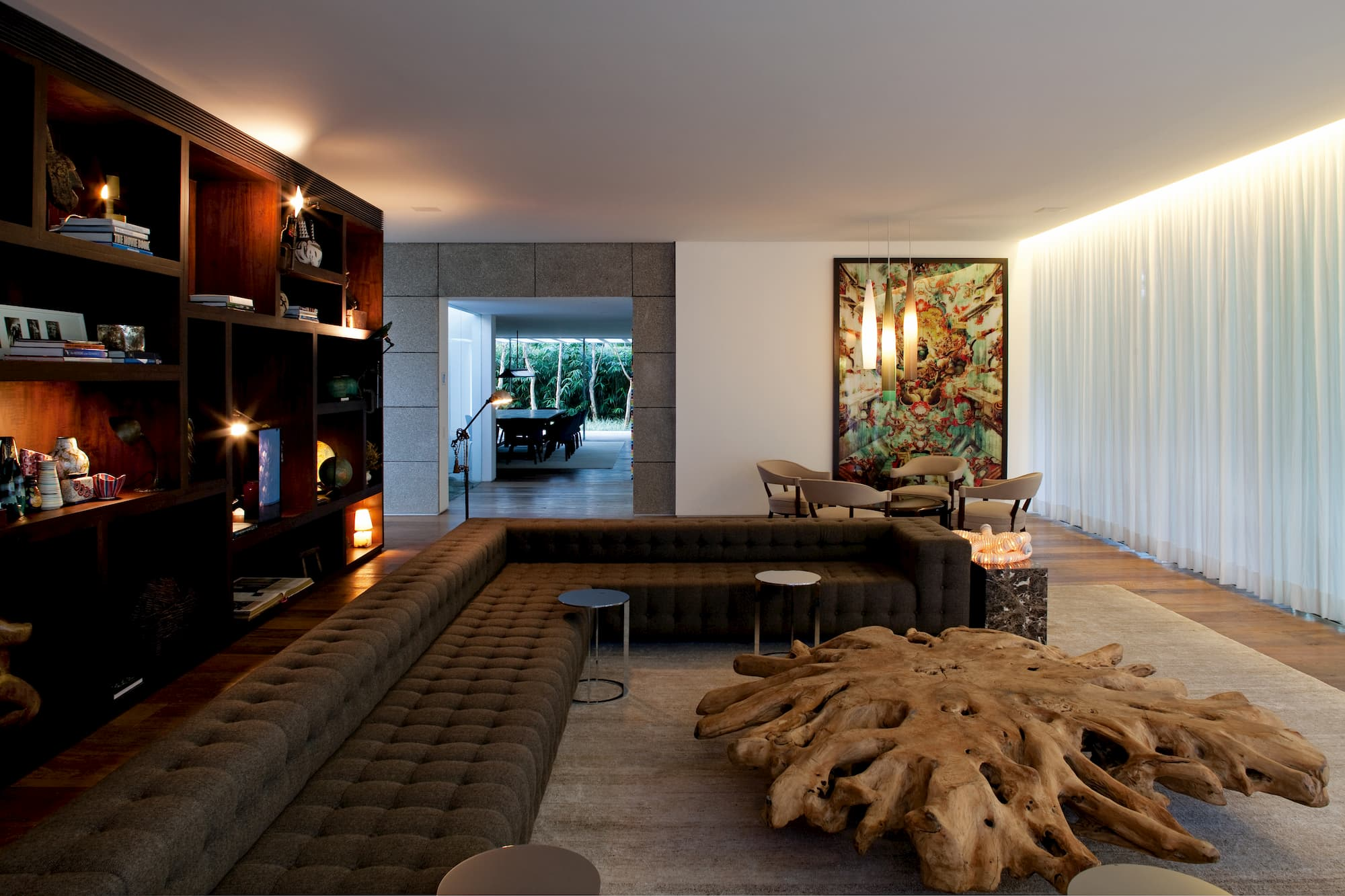 A unique living room with a giant brown-gray L-shaped sofa and a coffee table made of huge wooden roots. A white curtain covers an entire wall opposite a large wooden bookshelf, with a huge picture on the third wall