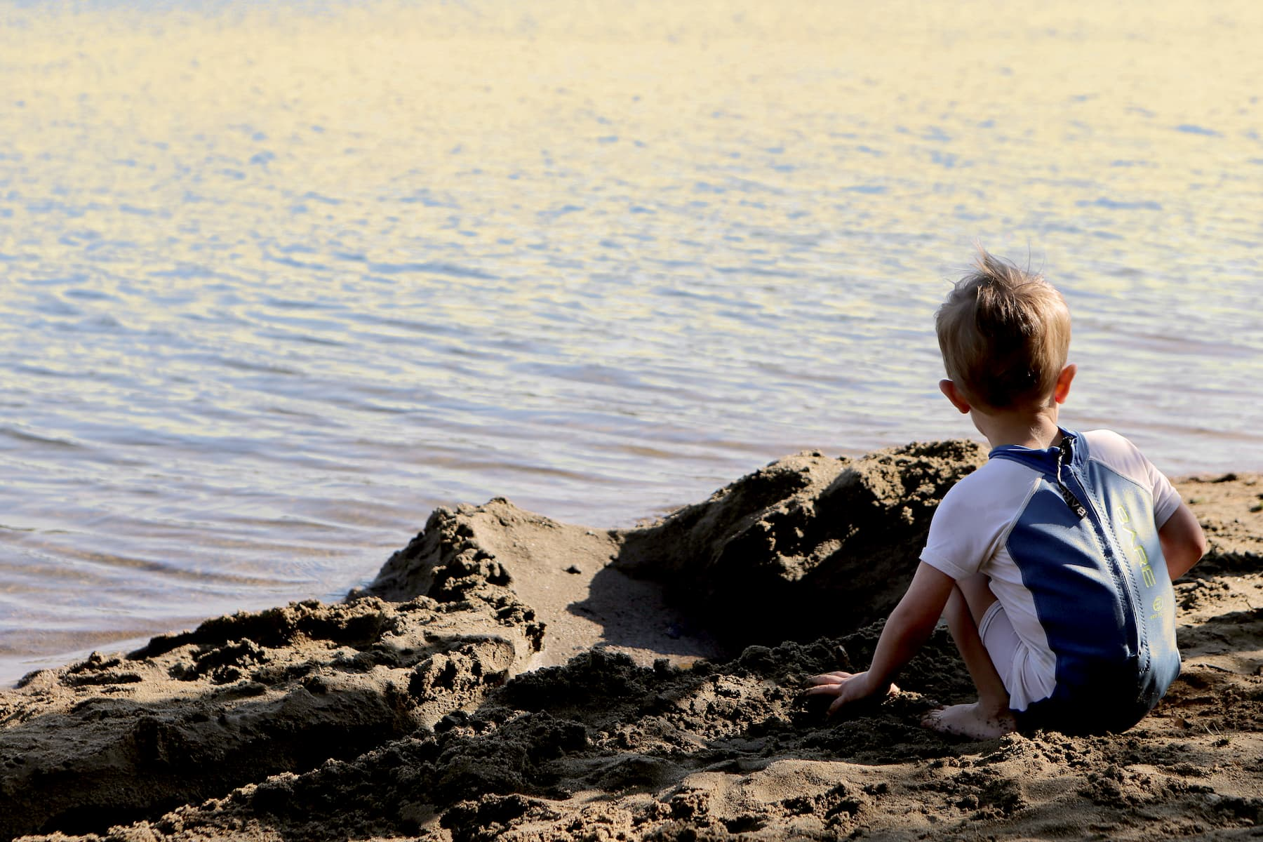 A barefoot boy with his hands in wet soil by the sea.