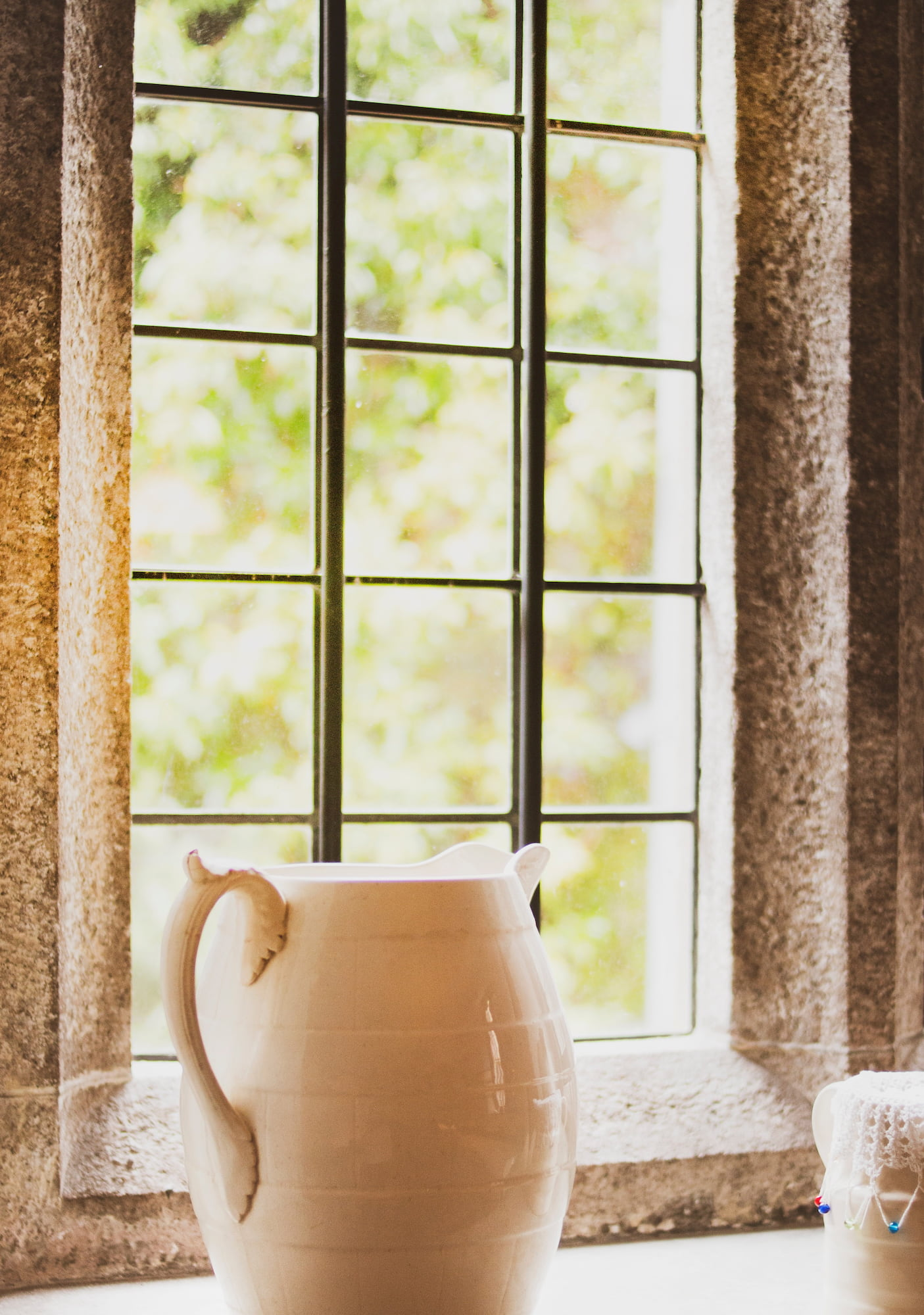 A white ceramic water jug rests on a window sill made of iron and surrounded by a stone frame