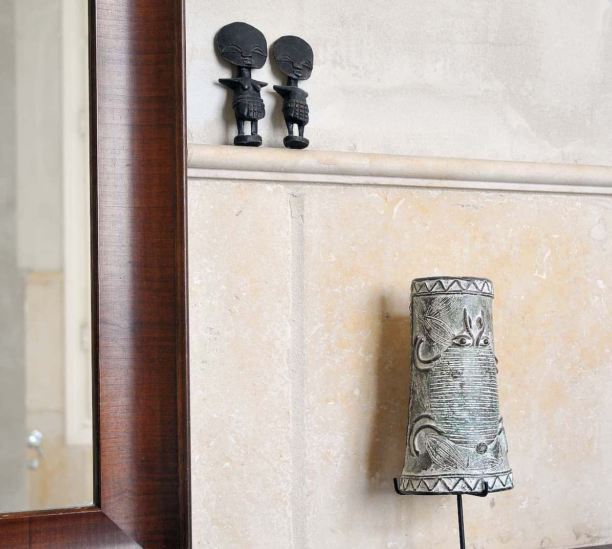 Decorative items: a stone wall, a ceramic lamp, iron figurines, and wood framed mirror.