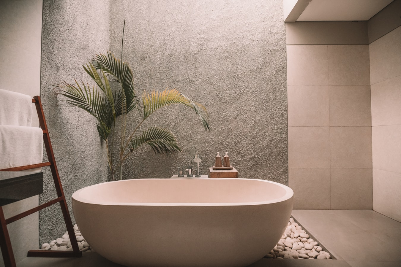 A stone bathtub set on pebbles in an open-air terrace with walls made of plaster and stone tiles.