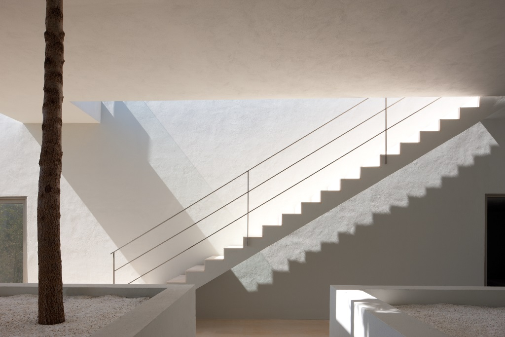 Light from above cascades down a white staircase with a minimalist horizontal metal railing.