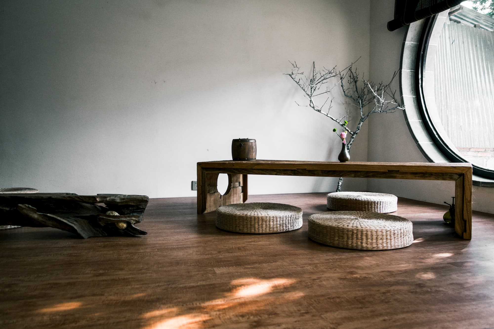 A simple wooden table and three round wicker cushions rest on a walnut floor with a tree branch resting in the corner as decoration.