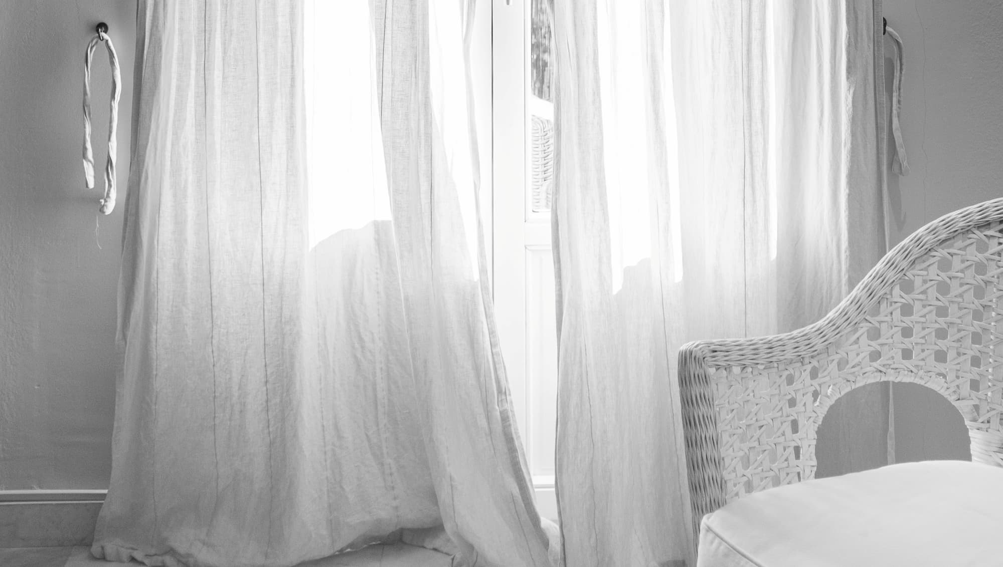 White light design - a wicker chair with a padded seat against a white cotton curtain.