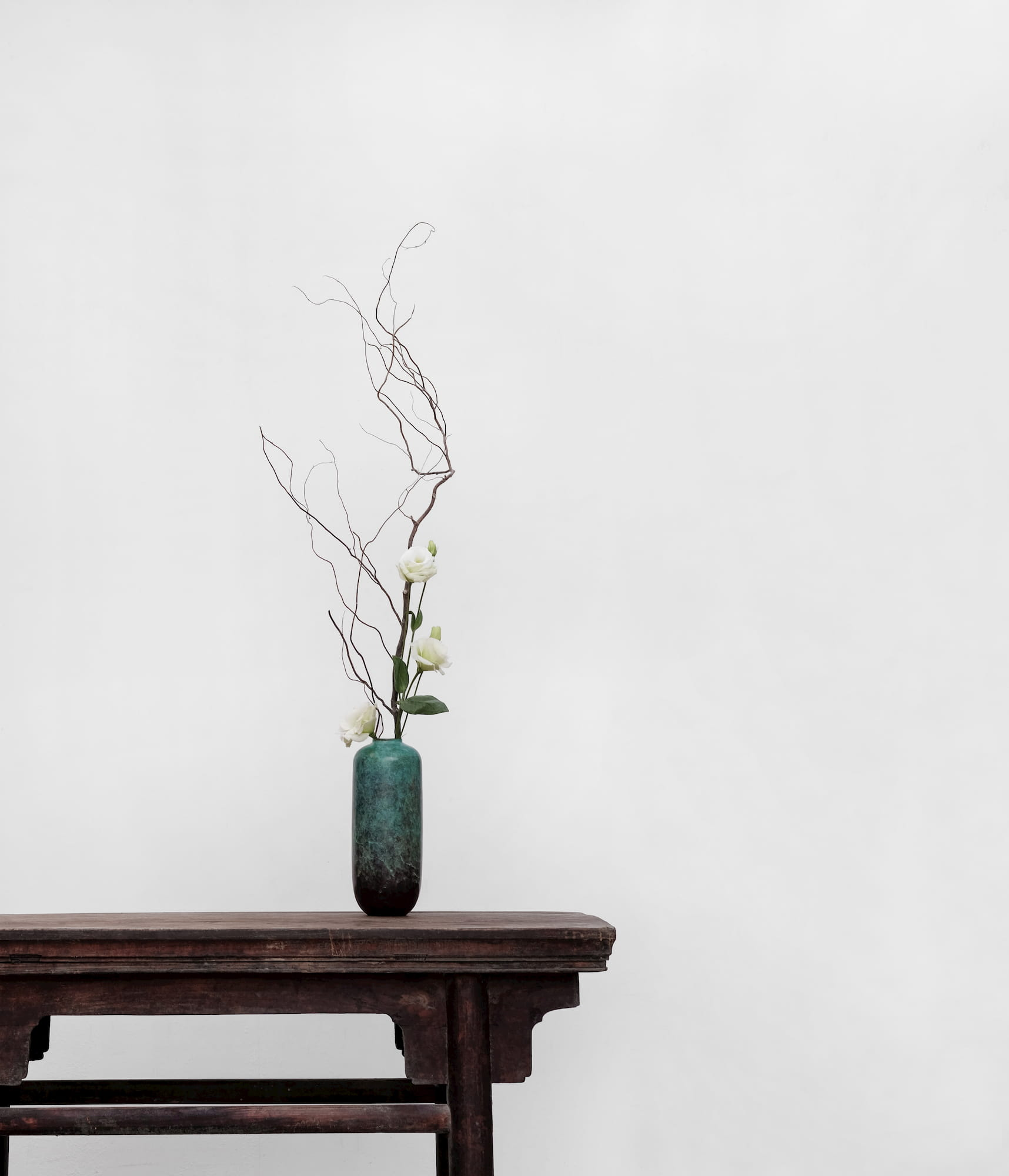 An arrangement of flowers and dry branches rises from a marbled vase resting at the edge of a dark wooden table.